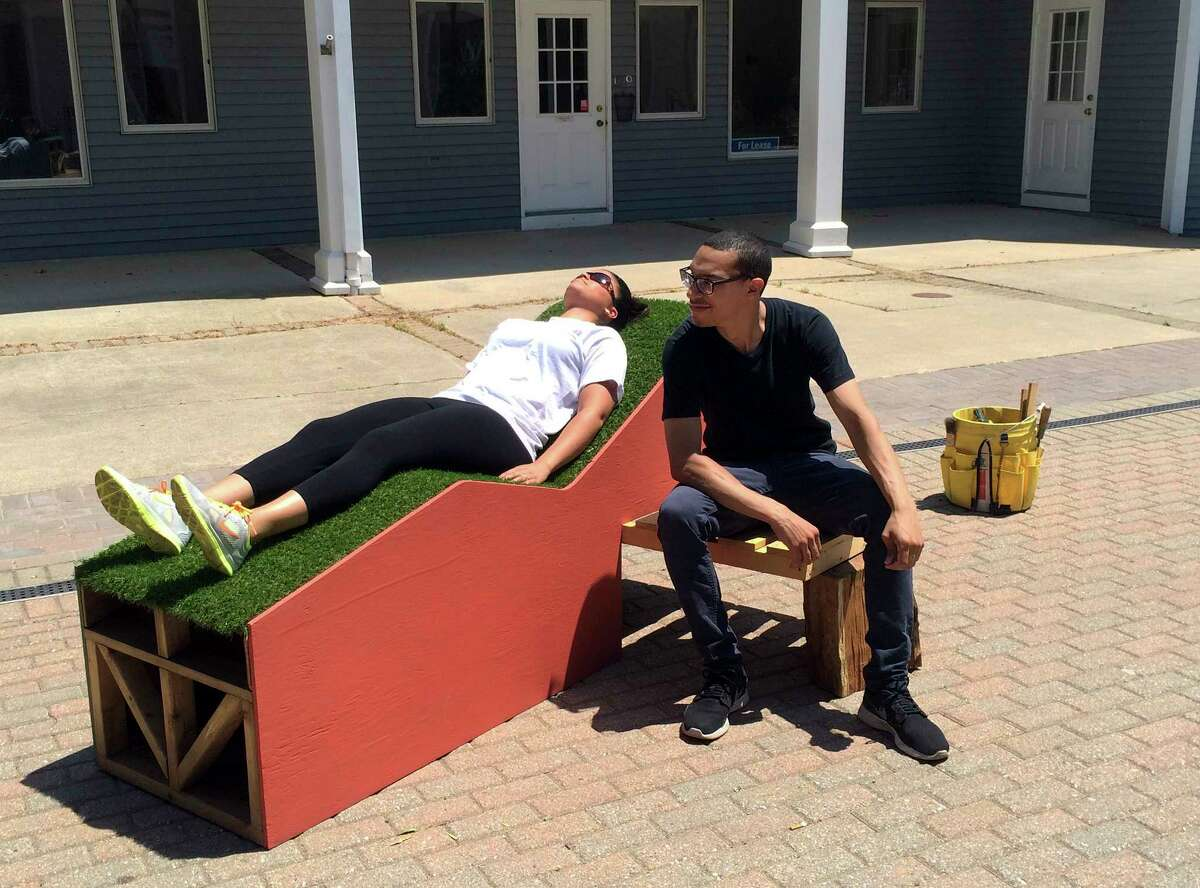 In this Sunday, June 14, 2015 photo provided by New York City artist Jim Osman, his assistant Alex Reyes, right, sits beside a passer-by lying on the wood and tile