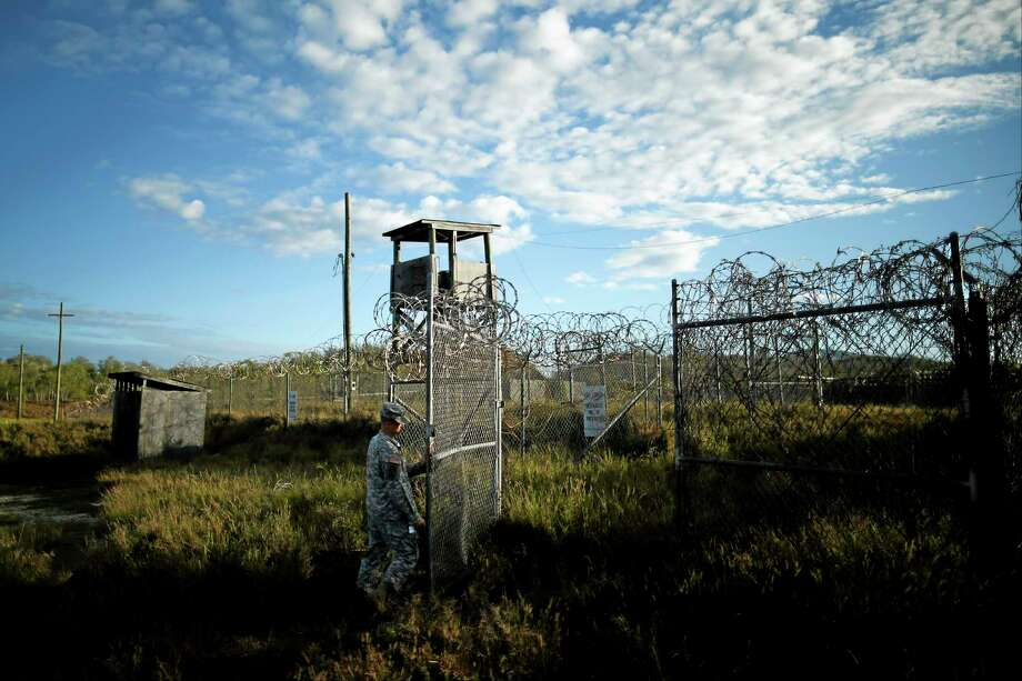 In this photo reviewed by the U.S. military, a soldier closes the gate at the now abandoned Camp X-Ray, which was used as the first detention facility for al-Qaida and Taliban militants who were captured after the Sept. 11 attacks at Guantanamo Bay Naval Base, Cuba, Thursday, Nov. 21, 2013.  Detainees were housed in open air pens until the completion of Camp Delta in April 2002. Many detainees at Guantanamo Bay may be closer to heading home under a bipartisan deal reached in Congress that gives President Barack Obama a rare victory in his fight to close the prison for terror suspects. (AP Photo/Charles Dharapak) Photo: AP / AP