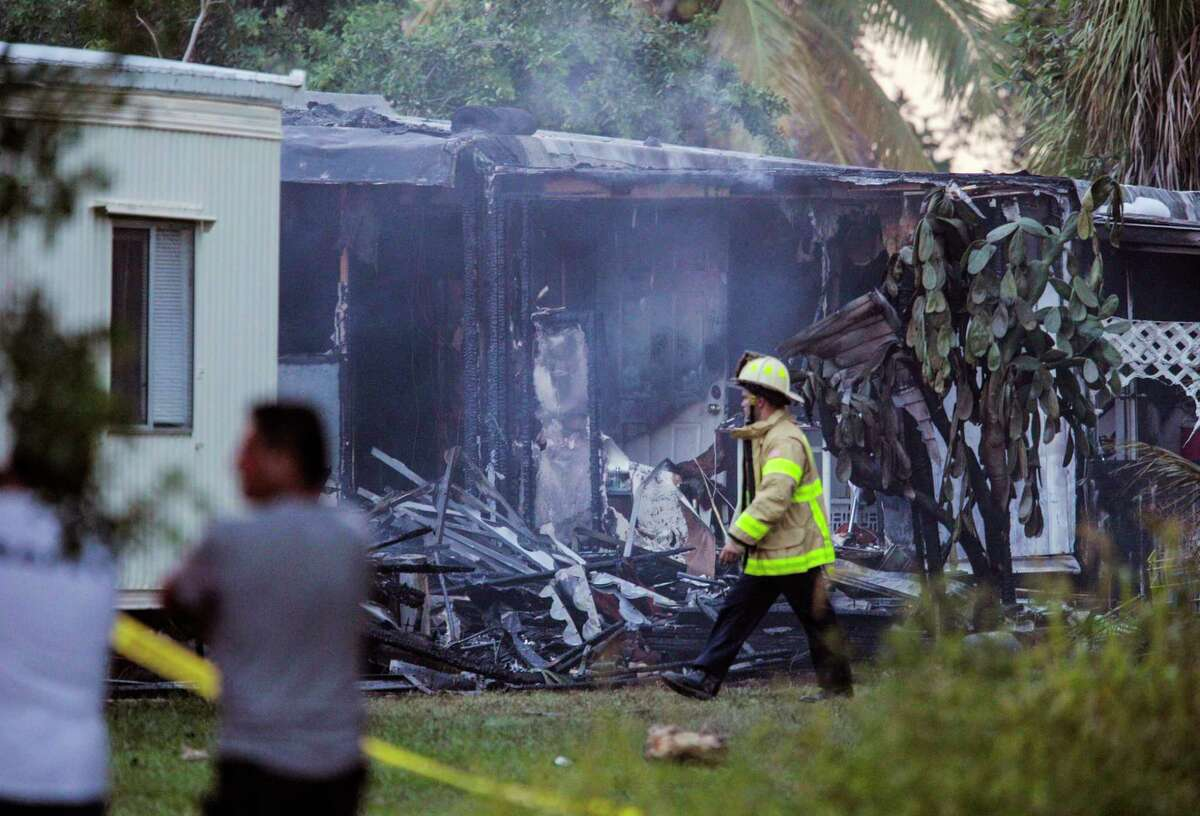 A firefighter walks by a charred mobile home that burned after a small plane crashed in suburban Lake Worth, Fla., Tuesday, Oct. 13, 2015. The aircraft hit several homes at the Mar-Mak Colony Club.