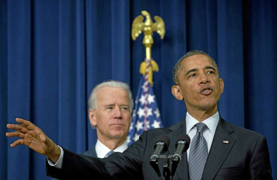 "FILE - In this Jan. 16, 2013 file photo, President Barack Obama, accompanied by Vice President Joe Biden, gestures as he talks about proposals to reduce gun violence, in the South Court Auditorium at the White House in Washington.  It was a moment for Barack Obama to savor. His second inaugural address over, Obama paused as he strode from the podium last January, turning back for one last glance across the expanse of the National Mall, where a supportive throng stood in the winter chill to witness the launch of his new term. ""I want to take a look, one more time,"" Obama said quietly. ""I'm not going to see this again.""There was so much Obama could not _ or did not _ see then, as he opened his second term with a confident call to arms and an expansive liberal agenda. (AP Photo/Carolyn Kaster, File) Photo: AP / AP"