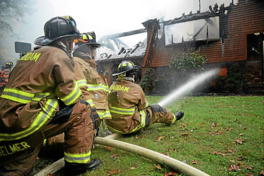 Haddam firefighters Jay Selmer, Joe Tomasso and Dan Dashelet work to extinguish a fire that destroyed a home and detached garage at 575 Candlewood Hill Road in Higganum Thursday. Photo: Olivia Drake — Special To The Press