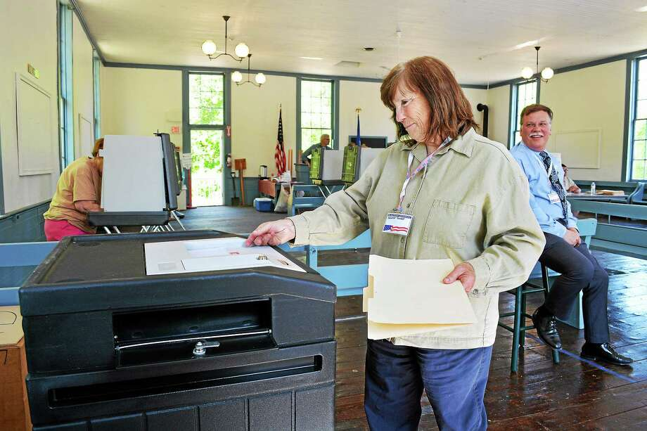 Catherine Avalone - The Middletown Press ¬ East Haddam resident Carol Loizeaux, a tabulator tender inserts her ballot during East Haddam's budget vote Tuesday afternoon at the Old Town Hall on Town Street in East Haddam. Edward Blaschik, also a tabulator tender keeps an eye on the optical scanner as residents cast their vote. Photo: Journal Register Co.