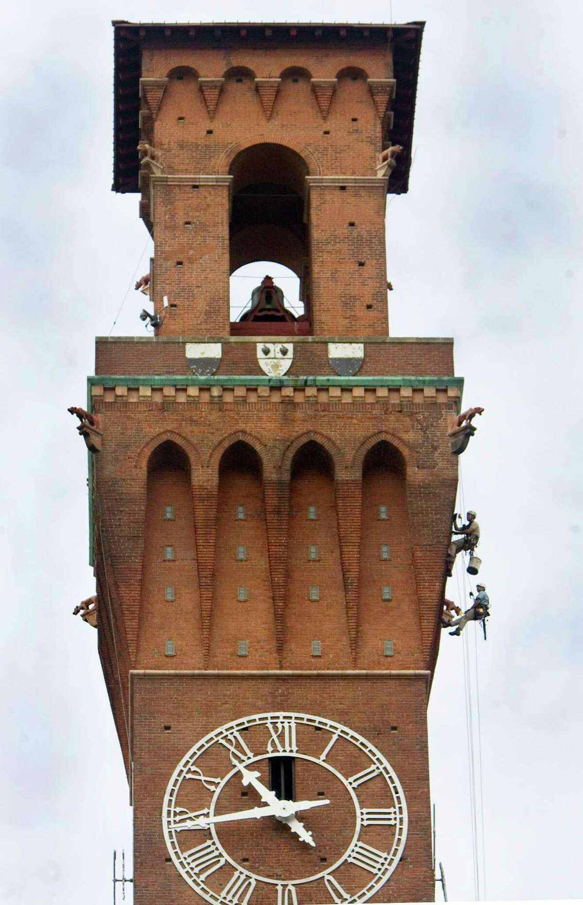Workers descend down the Republican-American's clock tower to investigate the condition of each face of the 240-foot-tall structure in Waterbury, Conn. Thursday June 18th 2015. The results of their inspection will be used to design repairs to the 109-year-old clock tower. (Steven Valenti/The Republican-American via AP) MANDATORY CREDIT