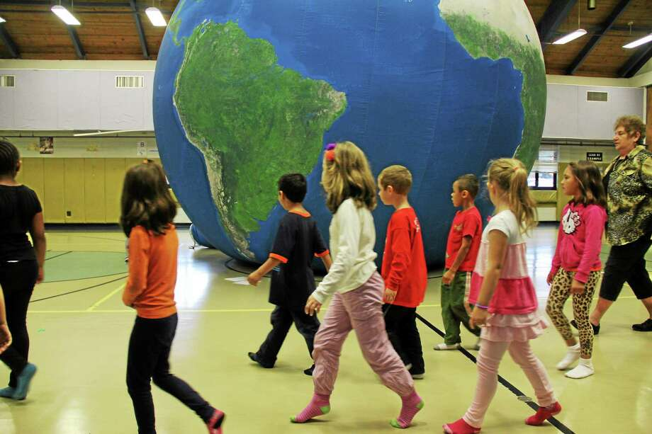 Earth Adventure brought its portable classroom, a 20-foot-diameter model of the earth made from high-resolution satellite images to Wesley School in Middletown. The program is designed to help students learn about the planet. Photo: Kathleen Schassler — The Middletown Press  / Kathleen Schassler All Rights