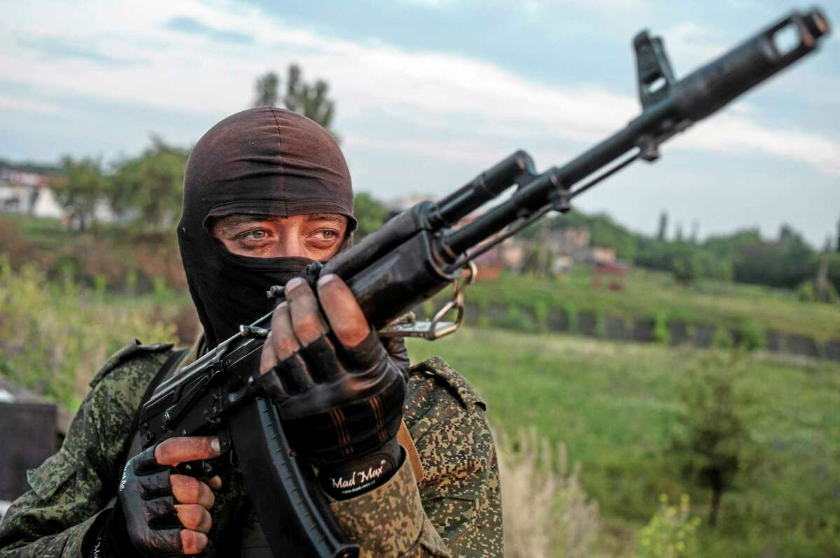 FILE - In this Wednesday, June 18, 2014, file photo, a pro-Russian fighter holds a gun during a handover of the bodies of Ukrainian troops killed in a plane shot down near Luhansk, at a checkpoint in the village of Karlivka near Donetsk, eastern Ukraine. Russia is resuming its military buildup along the Ukrainian border in an apparent attempt to intimidate its neighbor, NATO's chief said Thursday, June 19, 2014, as Ukrainian government forces unleashed a major offensive against pro-Moscow insurgents. (AP Photo/Evgeniy Maloletka, File)