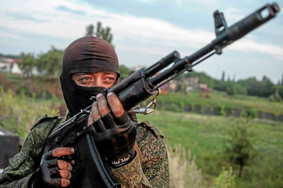 FILE - In this Wednesday, June 18, 2014, file photo, a pro-Russian fighter holds a gun during a handover of the bodies of Ukrainian troops killed in a plane shot down near Luhansk, at a checkpoint in the village of Karlivka near Donetsk, eastern Ukraine. Russia is resuming its military buildup along the Ukrainian border in an apparent attempt to intimidate its neighbor, NATO's chief said Thursday, June 19, 2014, as Ukrainian government forces unleashed a major offensive against pro-Moscow insurgents. (AP Photo/Evgeniy Maloletka, File) Photo: AP / AP