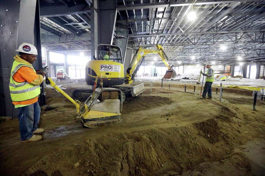 In this Oct. 1, 2014 photo, workers prepare an area for concrete in the planned casino floor of the Plainridge Park Casino, under construction adjacent to the Plainridge Racecourse harness racing track in Plainville, Mass. Photo: AP Photo/Steven Senne  / AP