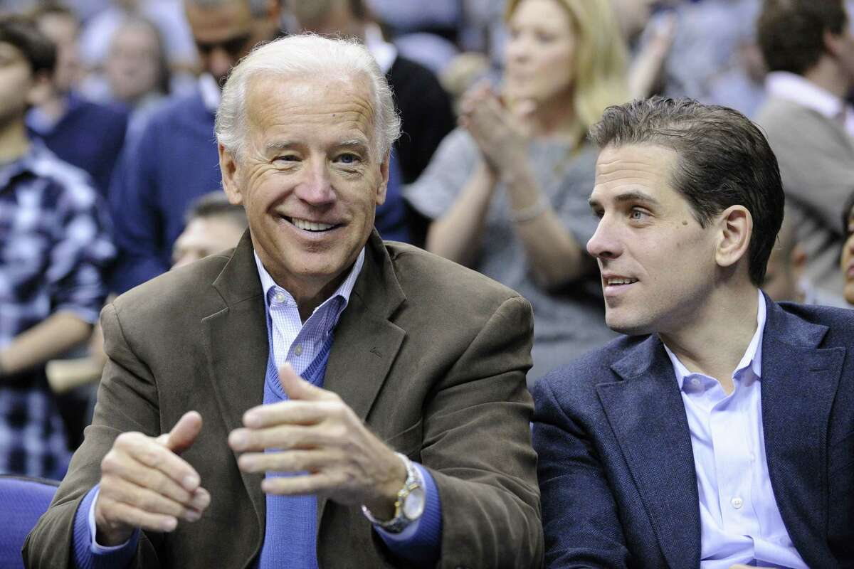 FILE - In this Jan. 30, 2010, file photo, Vice President Joe Biden, left, with his son Hunter, right, at the Duke Georgetown NCAA college basketball game in Washington. Hunter Biden is expressing regret for being discharged from the Navy Reserve amid published reports that he tested positive for cocaine. The Wall Street Journal reports that Hunter Biden failed the drug test last year and was discharged in February. In a statement issued Thursday, Oct. 16, Biden doesn't say why he was discharged. He says he's embarrassed that his actions led to his discharge and that he respects the Navy's decision. The vice president's office declined to comment.(AP Photo/Nick Wass, File)