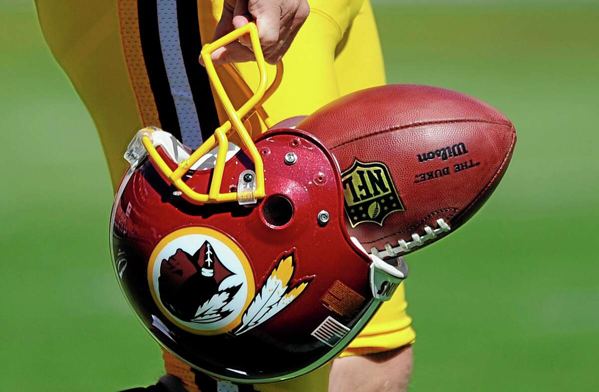 FILE - In this Sept. 23, 2012, file photo, Washington Redskins punter Sav Rocca carries a football in his helmet before an NFL football game against the Cincinnati Bengals in Landover, Md. The U.S. Patent Office ruled Wednesday, June 18, 2014, that the Washington Redskins nickname is