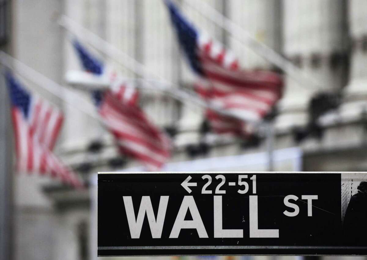 FILE - This April 22, 2010, file photo, shows a Wall Street sign in front of the New York Stock Exchange. Asian shares pushed higher Friday, June 19, 2015, following a rally in U.S. markets, but China's benchmark sank again on worries over the potential impact of a flurry of initial public offerings and moves by regulators to curb margin trading.
