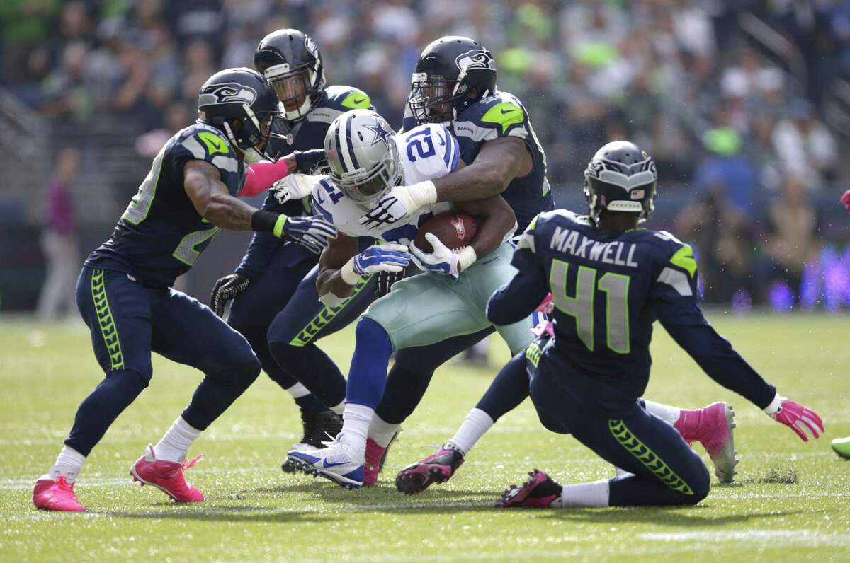 Dallas Cowboys running back Joseph Randle is tackled by a gang of Seahawks defenders in the first half of Sunday's game in Seattle.