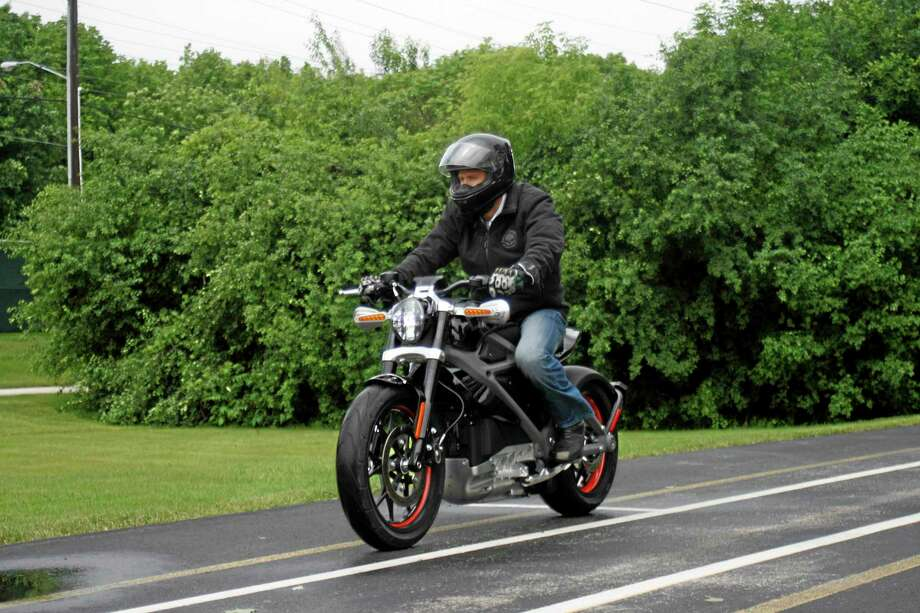 In this Wednesday, June 18, 2014 photo, employee Ben Lund demonstrates Harley's new electric motorcycle at Harley's research facility in Wauwatosa, Wis. The company plans to unveil the LiveWire model Monday, June 23, at an invitation-only event in New York. (AP Photo/M.L. Johnson) Photo: AP / AP