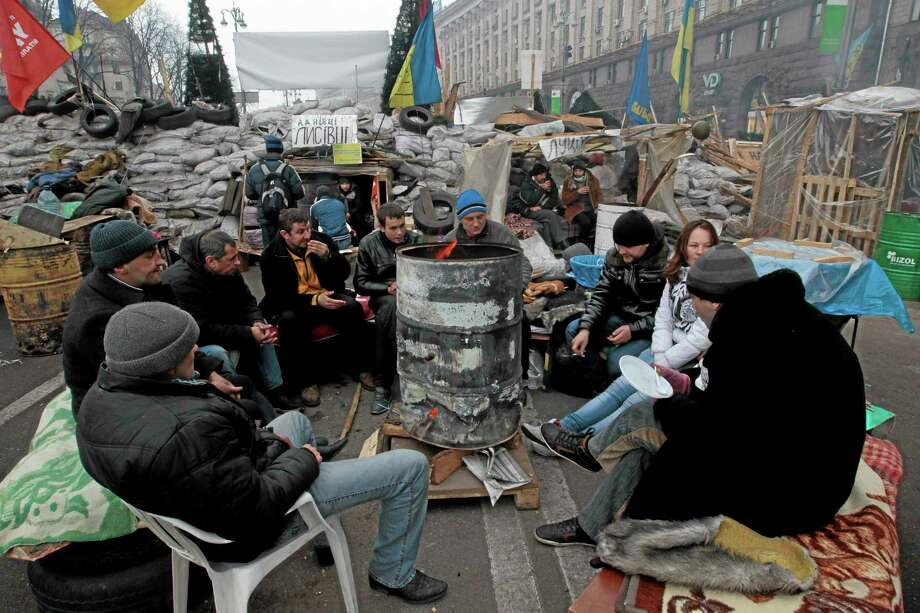 Pro-European Union activists warm themselves near a bonfire during a rally in Independence Square in Kiev, Ukraine, Thursday, Dec. 19, 2013. President Vladimir Putin says Russia's $15-billion bailout for Ukraine is driven by a desire to help a partner in a desperate situation and isn't linked to its talks with the European Union. The Kremlin's move comes as Ukrainian President Viktor Yanukovych faces massive street protests over his decision to spike a pact with the EU in favor of closer ties with Russia. (AP Photo/Sergei Chuzavkov) Photo: AP / AP