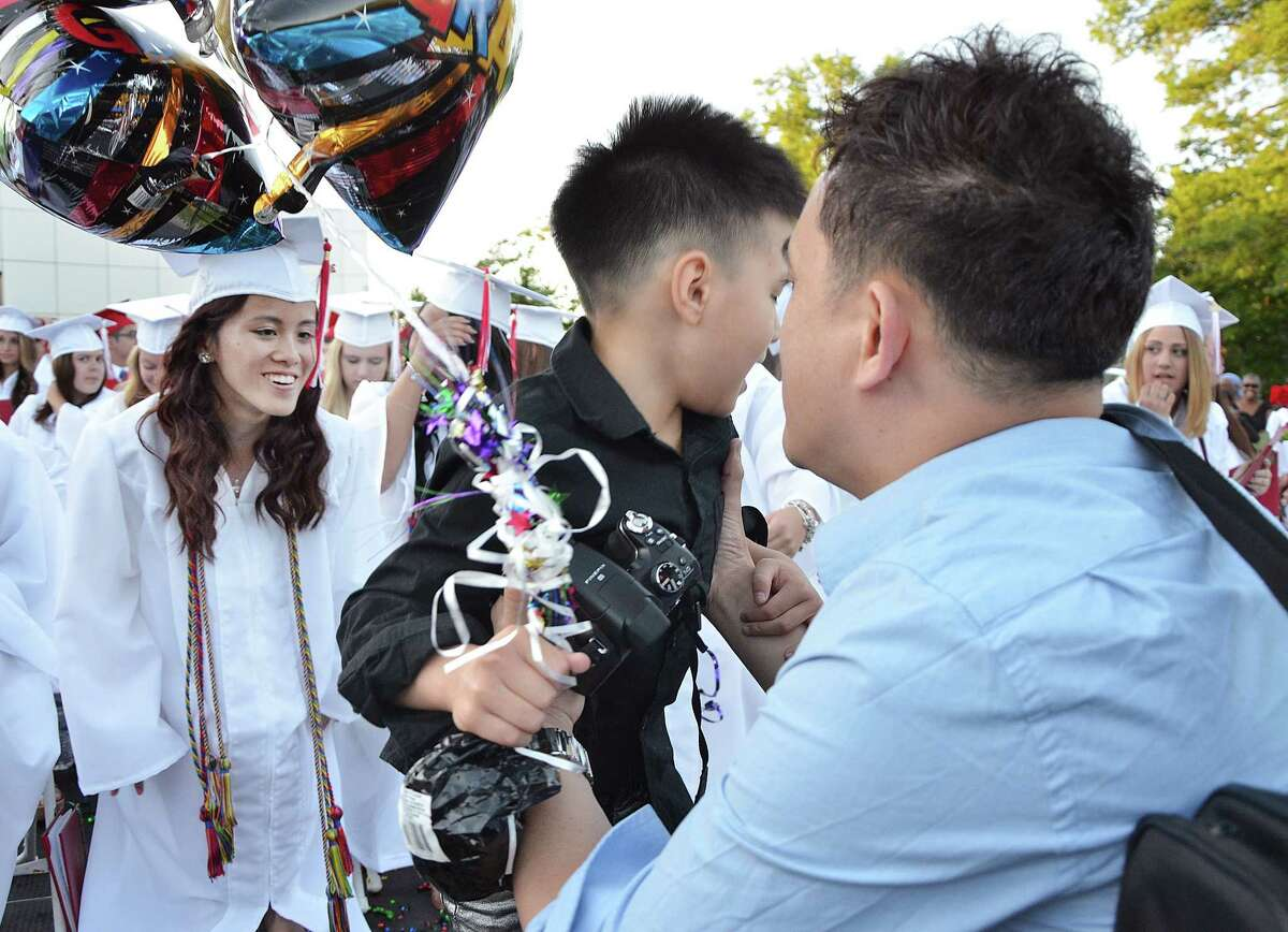 Catherine Avalone - The Middletown Press Cromwell High School graduate Vivian Chu gets a quick visit on stage from her little brother shortly after the class of 2014 received their diplomas Thursday evening.