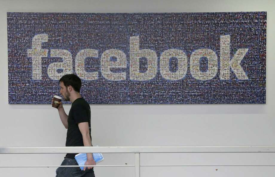 A Facebook employee walks past a sign at Facebook headquarters in Menlo Park, Calif. Photo: Jeff Chiu — The Associated Press  / AP