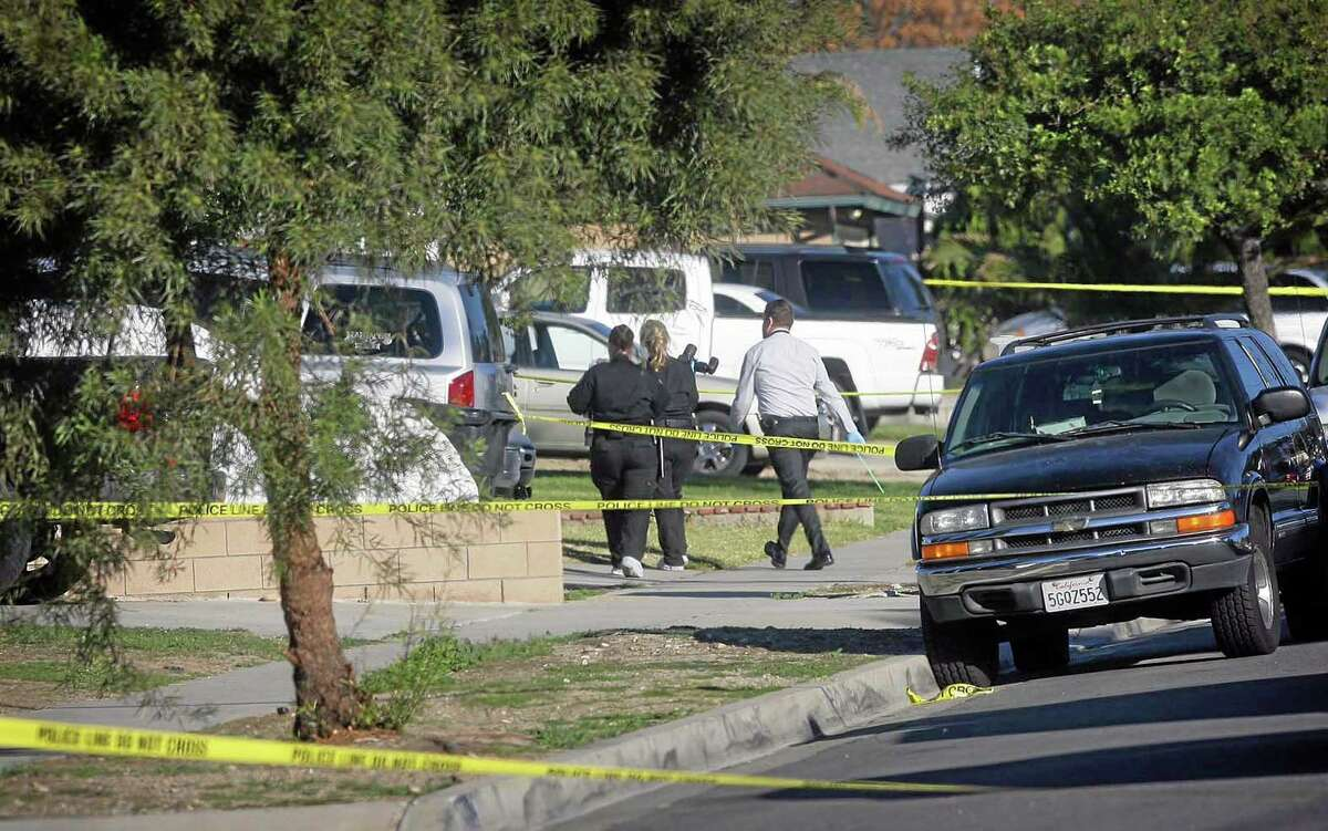 Fontana police crime scene investigators arrive at a home Tuesday where a family of four were found shot to death just before 10 p.m. Monday night in Fontana, Calif.