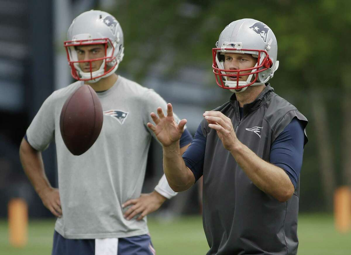 New England Patriots quarterback Tom Brady takes a snap as backup quarterback Jimmy Garoppolo looks on during minicamp Wednesday in Foxborough, Mass.