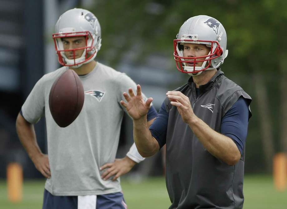 New England Patriots quarterback Tom Brady takes a snap as backup quarterback Jimmy Garoppolo looks on during minicamp Wednesday in Foxborough, Mass. Photo: Stephan Savoia — The Associated Press  / AP