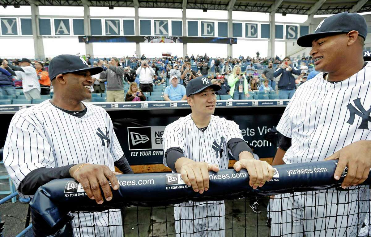New York Yankees starter Masahiro Tanaka, center, talks with teammates CC Sabathia, left, and Ivan Nova before their spring training game against the Pittsburgh Pirates on Thursday in Tampa, Fla.