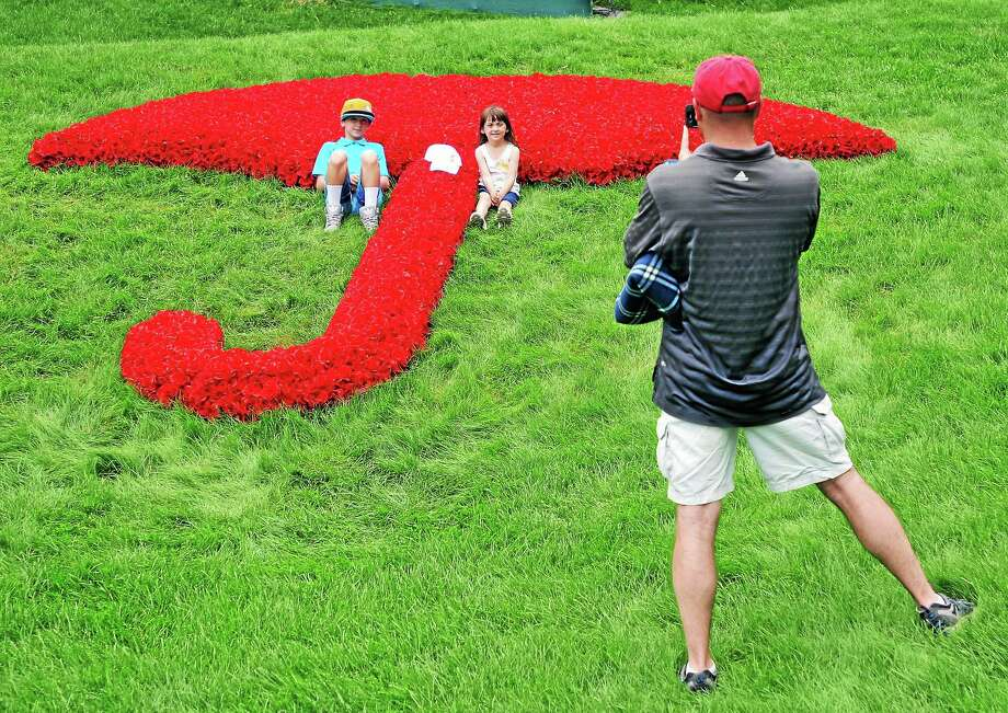 Mike Joyce of Wethersfield takes a photo of his children, Kylie, 12, and Eliza, 6, on the 18th green during the Travelers Celebrity Pro-Am on Wednesday at TPC River Highlands in Cromwell. Photo: Peter Casolino — Register