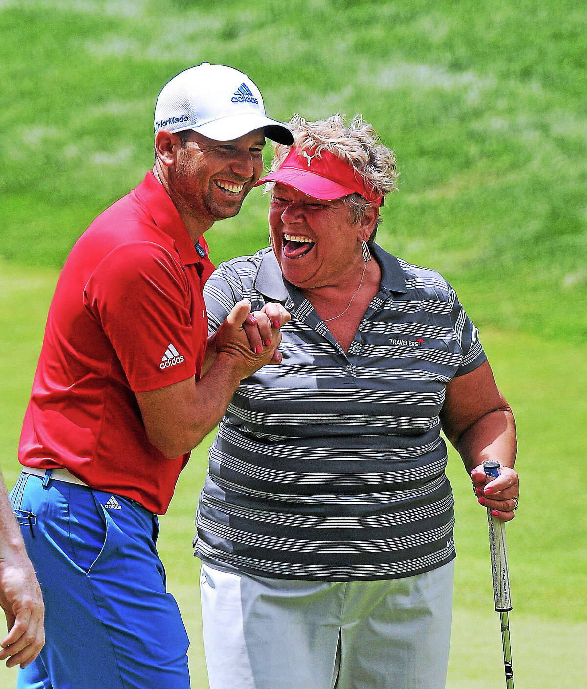 Sergio Garcia celebrates with amateur Barbara Pinkham after she sunk a 60-foot putt on the 18th hole during the Travelers Celebrity Pro-Am on Wednesday at TPC River Highlands in Cromwell.