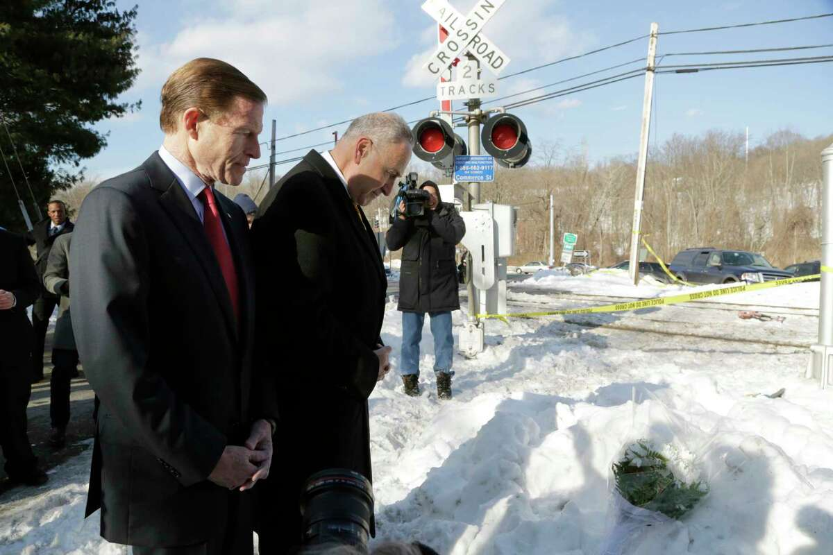 Sen. Richard Blumenthal, D-Conn., left, and Sen. Charles Schumer, D-N.Y., pause for a moment after placing a bouquet of flowers at a railroad crossing on Feb. 6 in Valhalla, N.Y. A car collided with a Metro-North Railroad train at the same location, killing the car's driver and five train passengers.