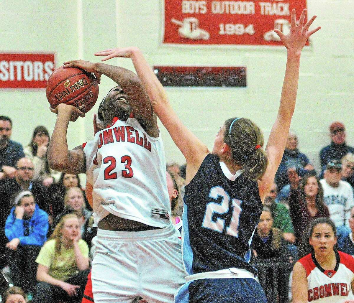 Cromwell's Janelle Harrison puts up a shot as Morgan's Josie Sullivan defends during the second quarter of the SLC Championship. Cromwell won 41-40 in overtime.
