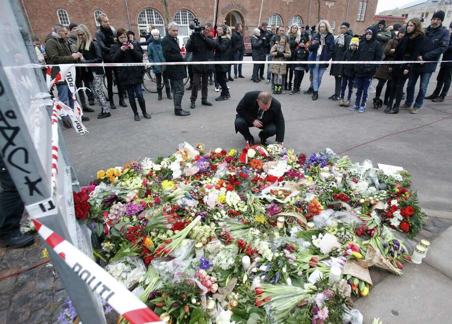 Flowers are placed in front of the cultural club where one person was killed in Copenhagen, Denmark, on Feb. 15, 2015. The alleged shooter was later killed by police who believe he also shot another person at a synagogue. Photo: AP Photo/Michael Probst  / AP
