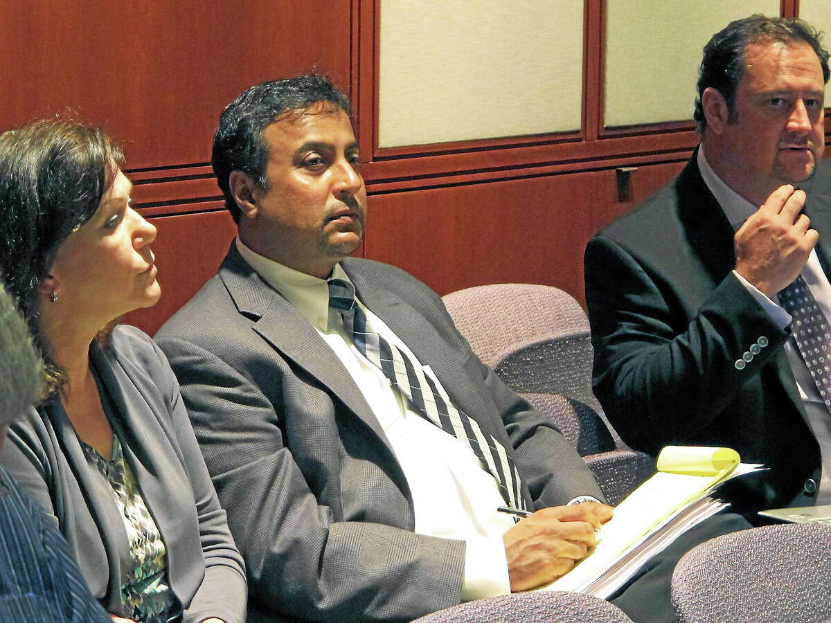 (AP Photo/Dave Collins) Dentist Rashmi Patel, middle, sits with supporters during a hearing before the Connecticut State Dental Commission on Wednesday, June 18, 2014, in Hartford, Conn.