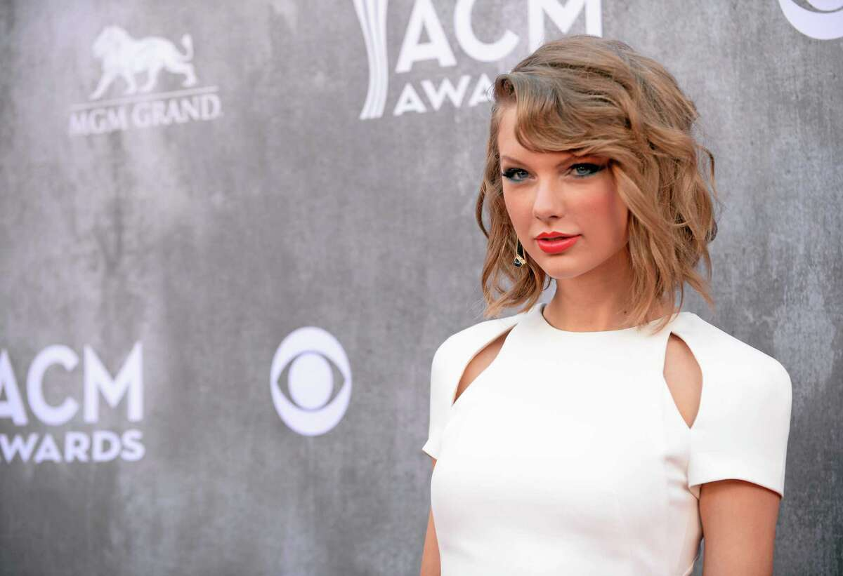 FILE - In this Sunday, April 6, 2014, file photo, Taylor Swift arrives at the 49th annual Academy of Country Music Awards at the MGM Grand Garden Arena in Las Vegas. Police in Rhode Island say they arrested three people outside Swiftís beachfront home after they accosted security guards at the singerís property. Authorities say the three Connecticut residents were charged with misdemeanor breach of peace after they threw beer bottles and shouted expletives at the guards Sunday, June 15, 2014, outside Swiftís house in the Watch Hill section of Westerly. Swift wasnít at the home at the time. (Photo by Al Powers/Powers Imagery/Invision/AP, File)