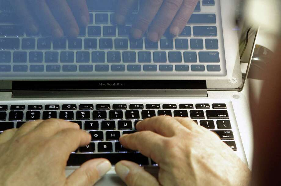This photo illustration shows hands typing on a computer keyboard. Photo: AP Photo / Damian Dovarganes2013