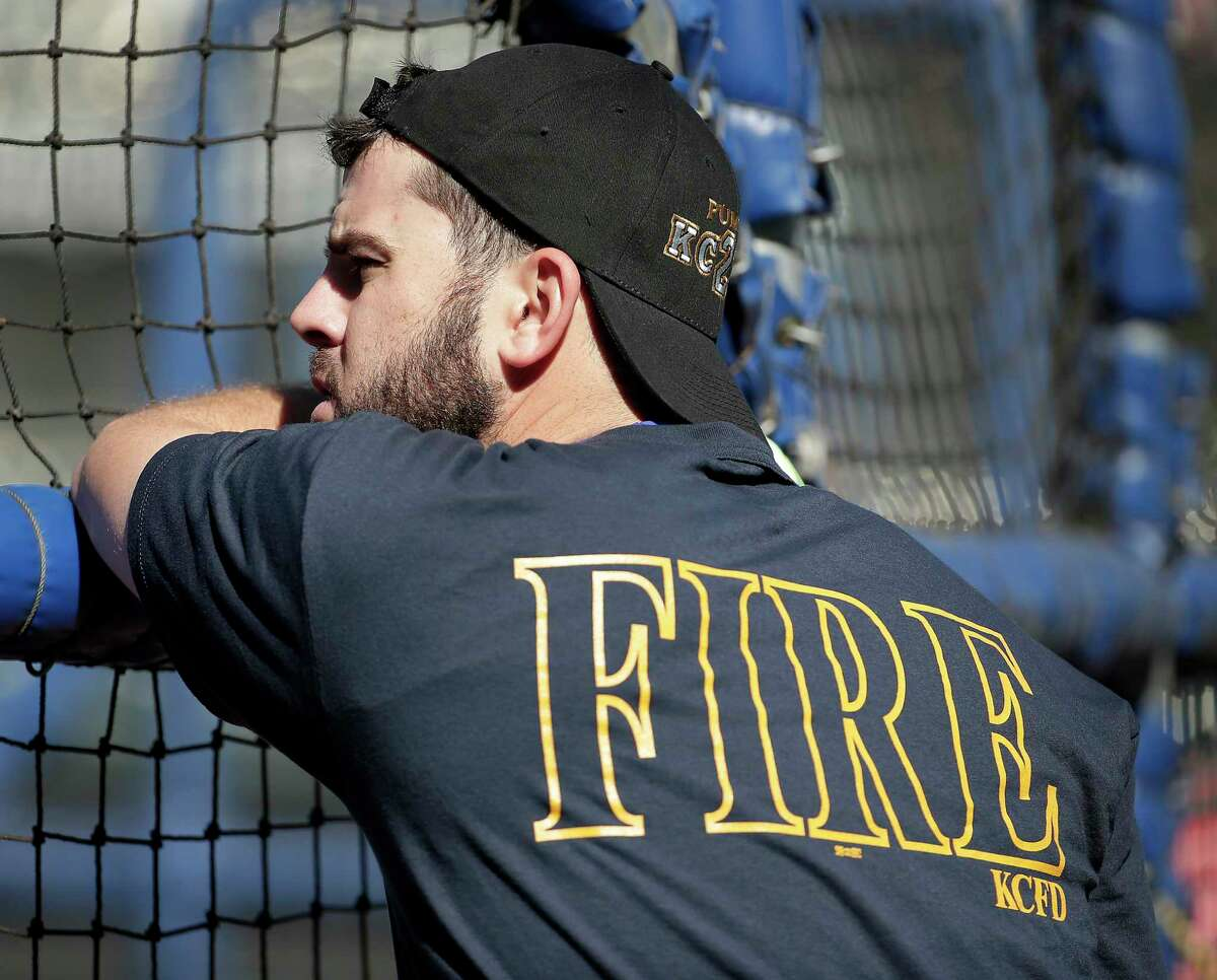 Royals third baseman Mike Moustakas wears Kansas City Fire Department apparel as he waits his turn during batting practice Tuesday in Kansas City, Mo.