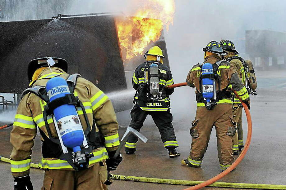 Olivia Drake - Special to the Press Firefighters from Haddam and other Middlesex County departments learn how to approach a vehicle fire at the Connecticut Fire Academy in Windsor Locks. Photo: Journal Register Co.