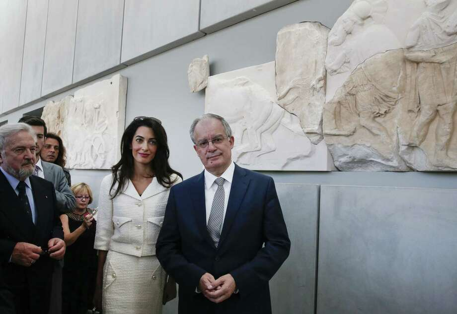 Lawyer Amal Clooney and Greek Minister of Culture and Sports Konstantinos Tasoulas, right, listens during a visit at the Parthenon hall inside the Acropolis museum in Athens, Wednesday Oct. 15, 2014. Lawyers Geoffrey Robertson, Norman Palmer and Amal Clooney arrived Monday to Greece on a four-day visit to meet government officials, including Prime Minister Antonis Samaras, and advise on Greece's quest to have the Parthenon Marbles returned to Athens. (AP Photo/Yorgos Karahalis, Pool) Photo: AP / Reuters Pool