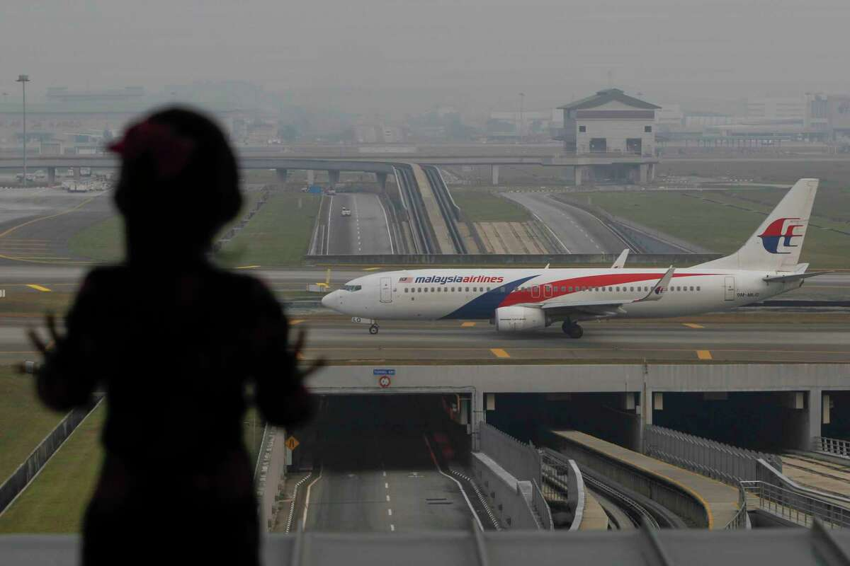 A young girl looks at a Malaysian Airlines aircraft taxiing on the runway of Kuala Lumpur International Airport in Sepang, Malaysia, Tuesday, Oct. 13, 2015. A Russian state-controlled missile-maker said Tuesday its investigation of last year's crash of a Malaysia Airlines plane over rebel eastern Ukraine contradicts conclusions from a Dutch probe.