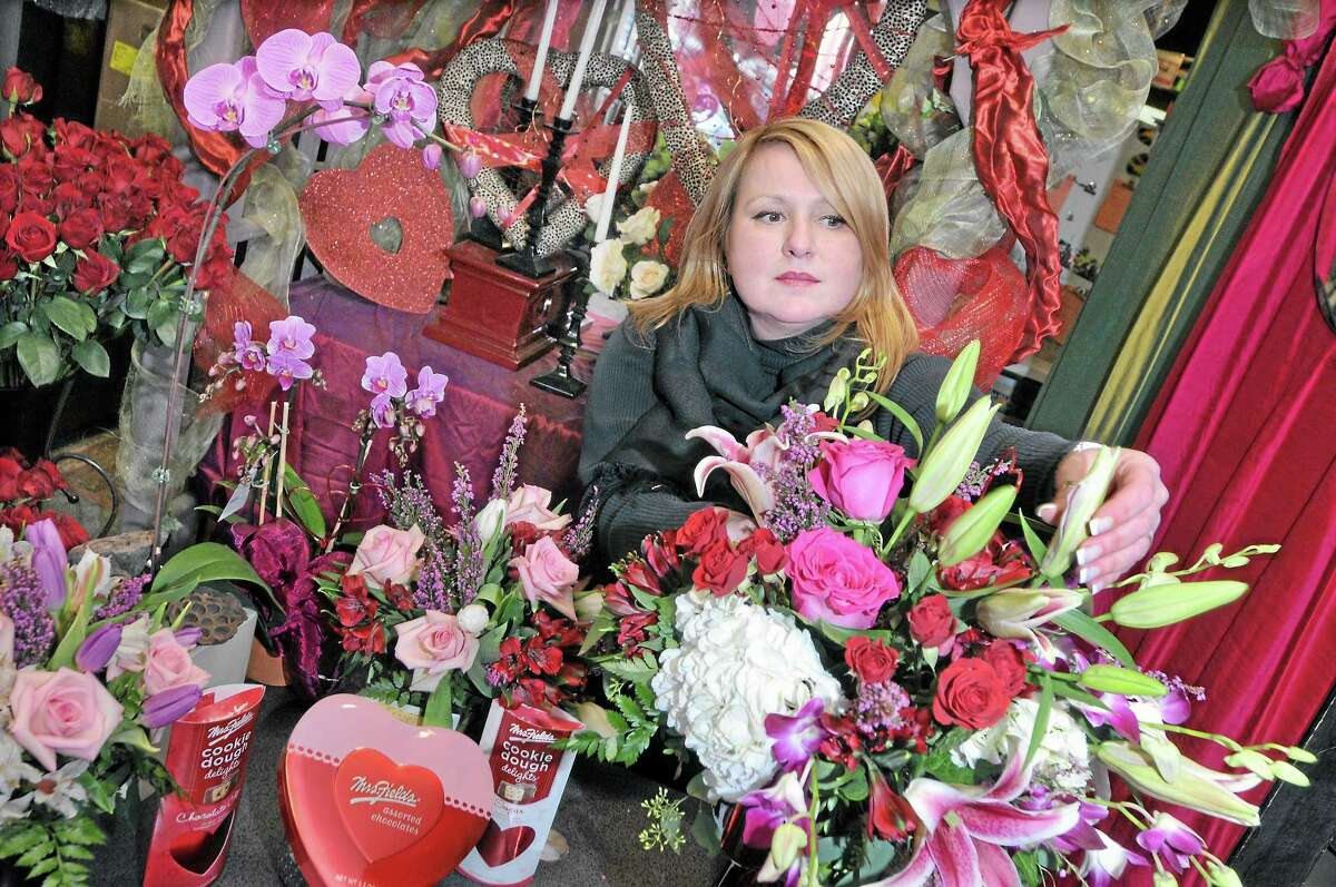 Virginia Wade-Fralick, co-owner and floral designer of Wild Orchid LLC at 413 Main Street in Middletown, adds orchids and lilies to an Valentine's Day arragement in this file photo.