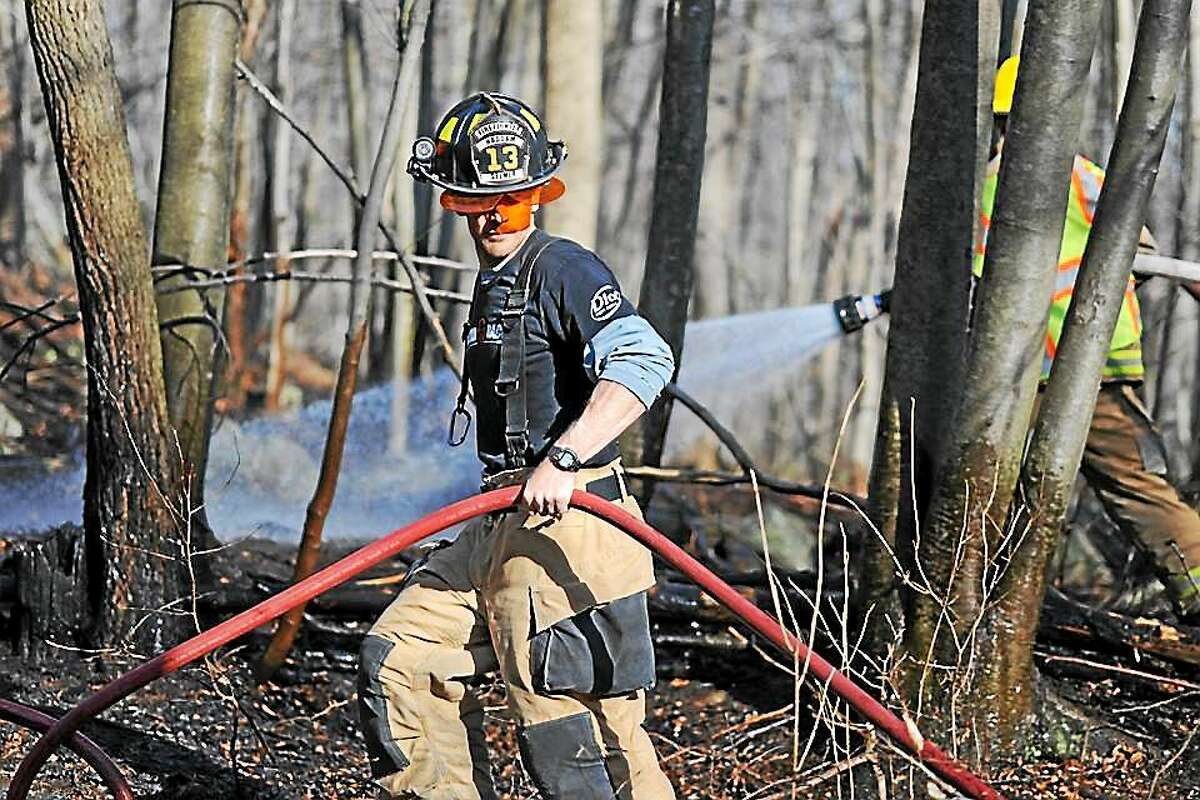 Haddam Firefighter Jay Selmer extends a hose line at a wildfire. Connecticut is experiencing its fall wildfire season.