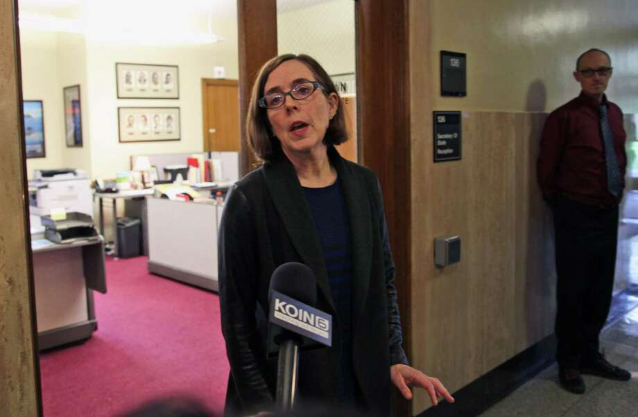 Oregon Secretary of State Kate Brown speaks to the media outside of her office at the Oregon Capitol in Salem, Ore., on Friday, Feb. 13, 2015. Brown will take over as governor after John Kitzhaber announced his resignation on Friday amid a growing ethics scandal involving his fiancee, a green-energy consultant accused of using her relationship with the governor to land contracts for her business. (AP Photo/Gosia Wozniacka) Photo: AP / AP
