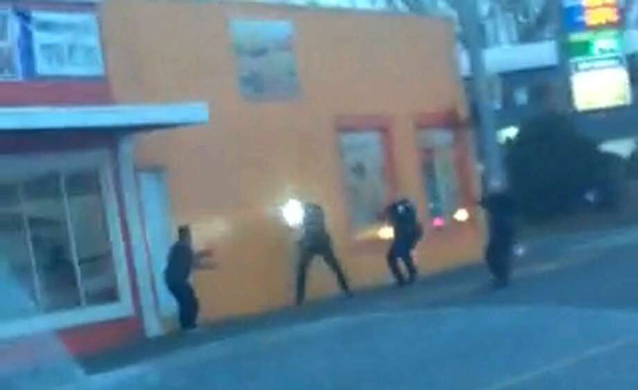 In this still frame taken from a cell phone video provided by Dario Infante and taken on Feb. 10, 2015, Antonio Zambrano-Montes, left, turns to face police officers as one holds a flashlight and two others draw their guns just before shooting him in Pasco, Wash.  Pasco police said Zambrano-Montes threw multiple rocks, hitting two officers, and refused to put down other stones, and witnesses said he was running away when officers shot and killed him. (AP Photo/Dario Infante) Photo: AP / Dario Infante
