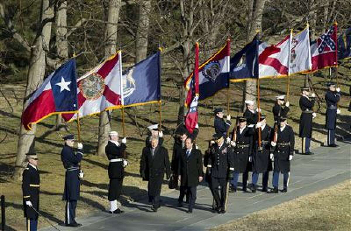 French President Francois Hollande, accompanied by Defense Secretary Chuck Hagel, arrives for the wreath laying ceremony at the Tomb of the Unknowns at Arlington National Cemetery in Arlington, Va., Tuesday, Feb. 11, 2014. (AP Photo/Jose Luis Magana)