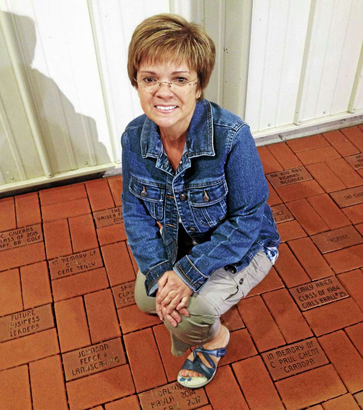Project Manager Connie Wache shows off the new brick walkway installed in front of the snack bar at the high school athletic fields in Portland, a project of the Sideliners.