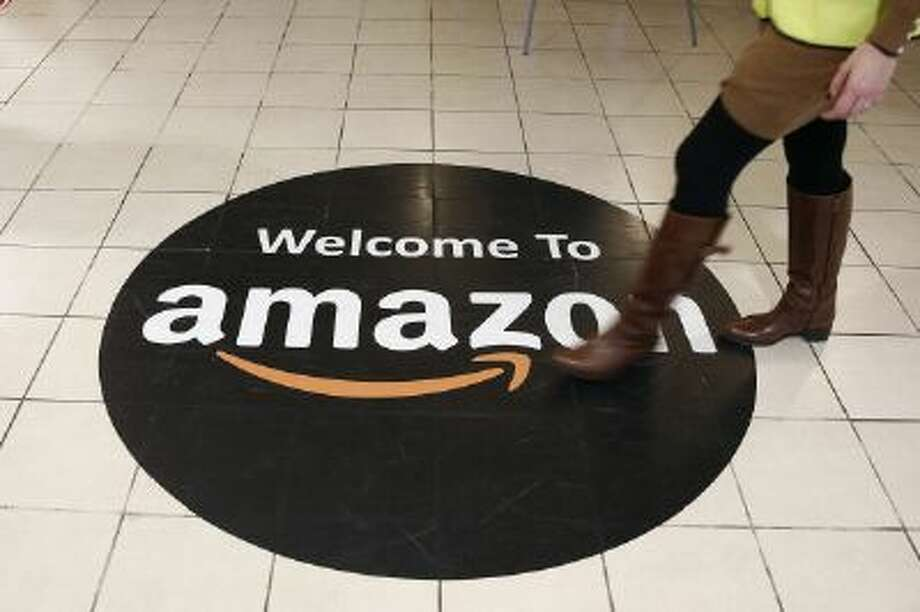 An employee walks over a logo on the floor of Amazon.com Inc.'s fulfillment centers in Rugeley, U.K., on Monday, Dec. 2, 2013. Online retailers in the U.K. are anticipating their busiest day as shoppers flush with end-of-month pay-checks seek Christmas deals on the Web. Photographer: Simon Dawson/Bloomberg via Getty Images Photo: Bloomberg Via Getty Images / 2013 Bloomberg