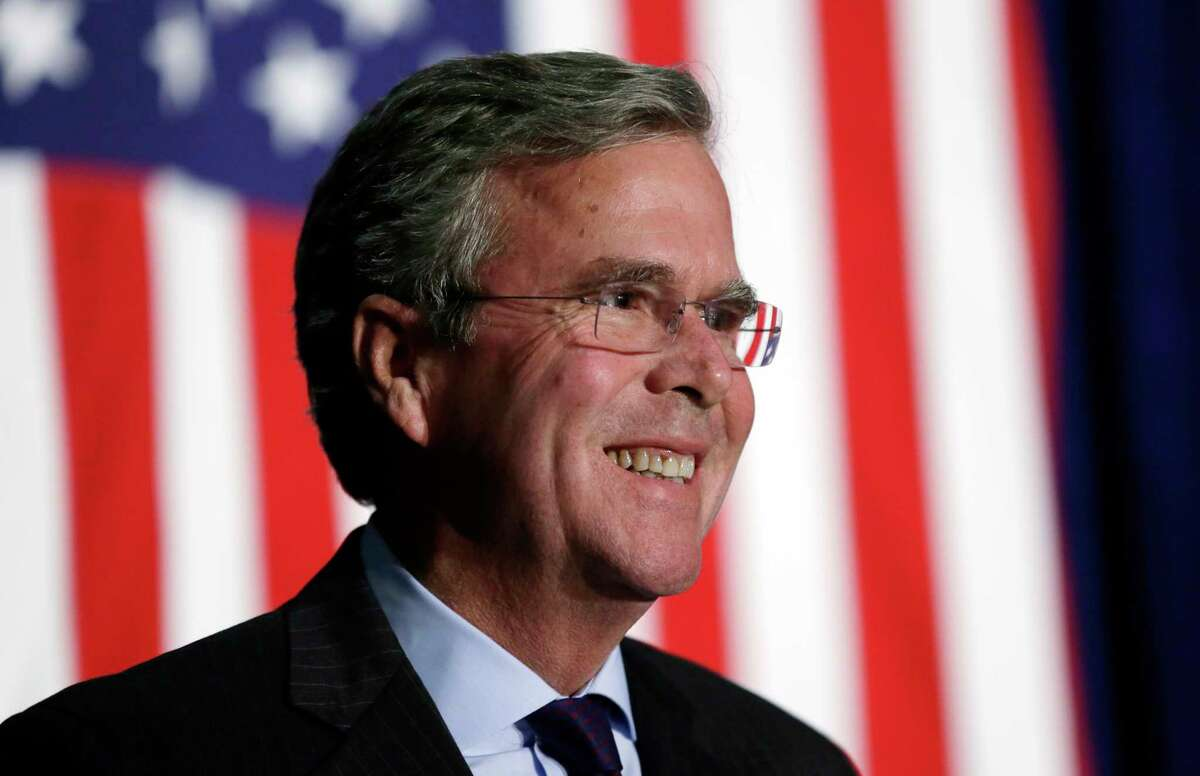 In this Oct. 6, 2015, file photo, Republican presidential candidate former Florida Gov. Jeb Bush reacts to a supporter during the Scott County Republican Party's Ronald Reagan Dinner in Davenport, Iowa. Bush is proposing to repeal and replace President Barack Obama's signature federal health care law. The former Florida governor released a two-page plan Oct. 12 to increase tax credits for individuals to buy coverage and give more power to states to regulate health insurance.