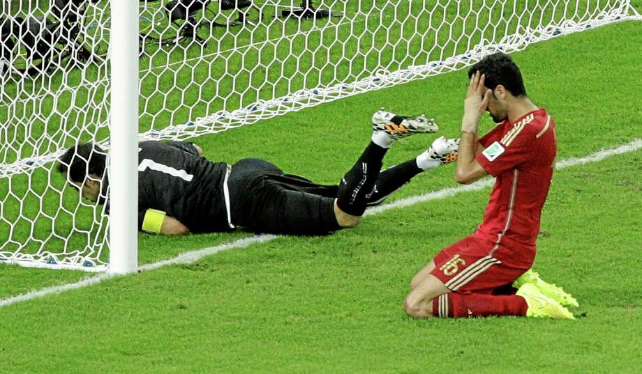 Spain's Sergio Busquets, right, holds his head after failing to score past Chile's goalkeeper Claudio Bravo during a group B World Cup match Wednesday at the Maracana Stadium in Rio de Janeiro. Photo: Christophe Ena — The Associated Press  / AP