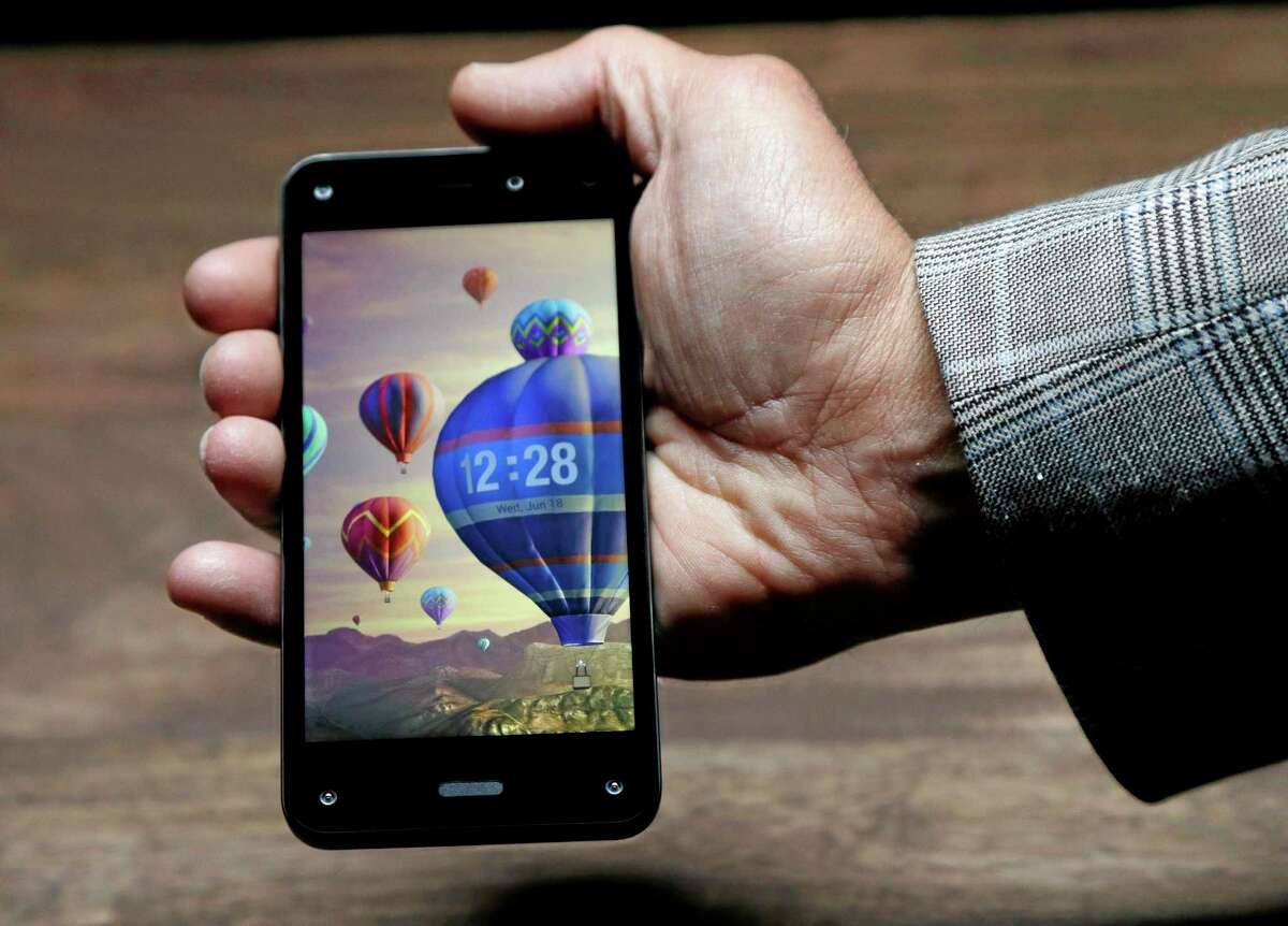 The new Amazon Fire Phone, displaying a dynamic perspective effect lock screen image, is posed for cameras after the official launch event Wednesday in Seattle.