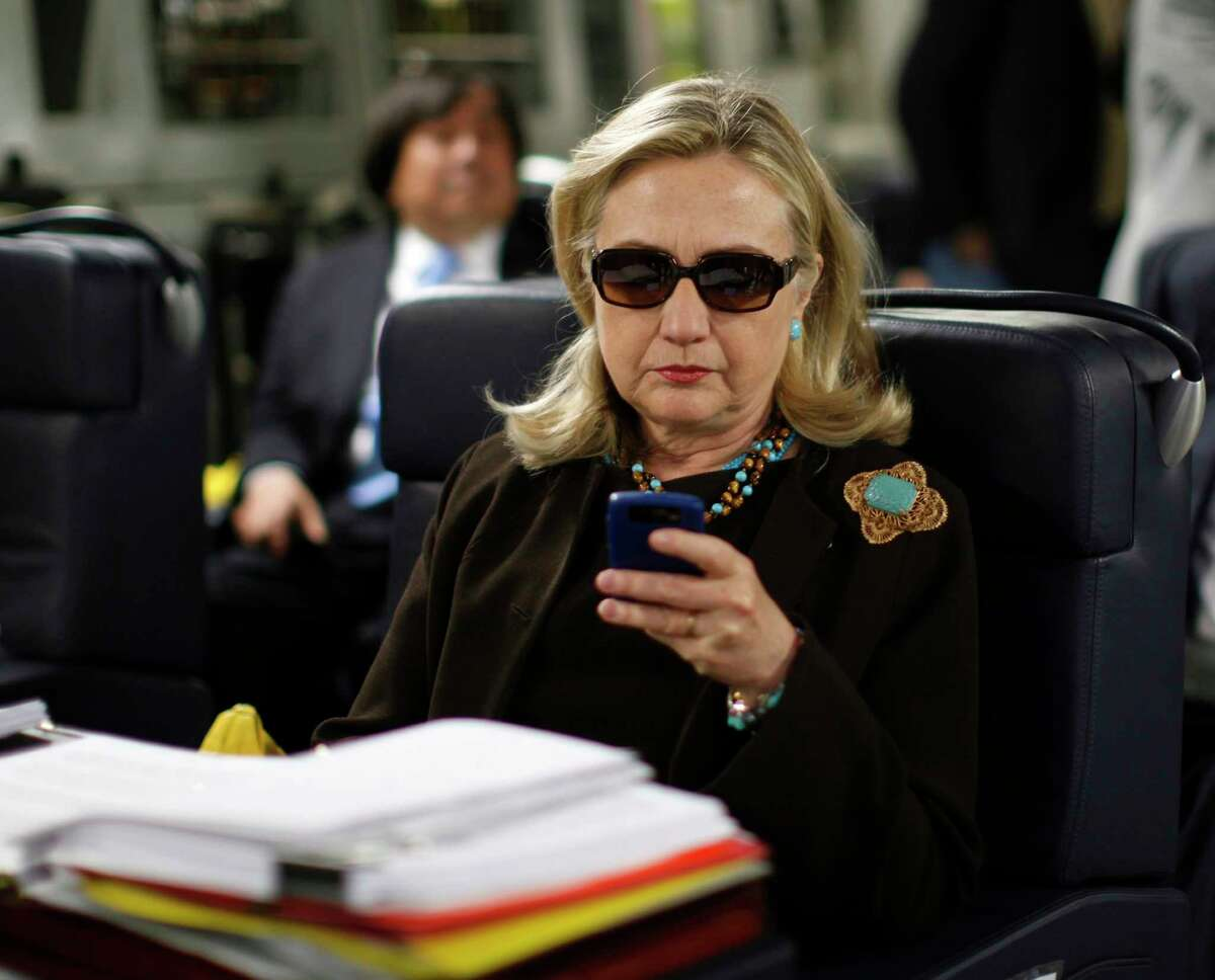 In this Oct. 18, 2011, file photo, then-Secretary of State Hillary Rodham Clinton checks her Blackberry from a desk inside a C-17 military plane upon her departure from Malta, in the Mediterranean Sea, bound for Tripoli, Libya. The private email server running in Clinton's home basement when she was secretary of state was connected to the Internet in ways that made it more vulnerable to hackers, according to data and documents reviewed by The Associated Press.