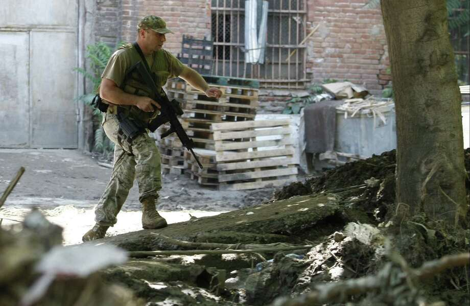 An armed police officer walks near a Zoo in Tbilisi, Georgia, Wednesday, June 17, 2015. Police in the ex-Soviet republic of Georgia reported that a tiger that broke loose after severe flooding at the Tbilisi Zoo was hiding at an abandoned factory when it mauled a man to death Wednesday before being shot by police. (AP  Photo/Shakh  Aivazov) Photo: AP / AP