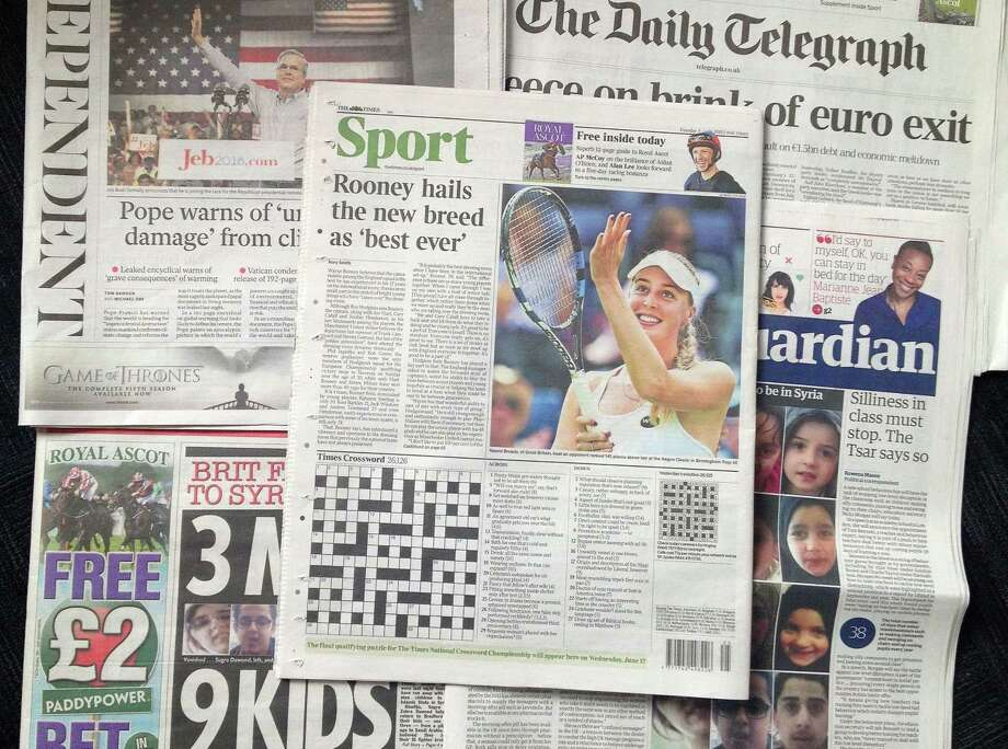 A combo taken on Wednesday June 17, 2015 showing some of the British national newspapers of Tuesday June 16 and featuring at centre the back page of The Times showing it's daily crossword puzzle. A crossword-loving British lawyer hid a marriage proposal in Tuesday's edition of The Times newspaper's daily puzzle. Matthew Dick thought of the cryptic way of popping the question to girlfriend Delyth Hughes, and persuaded the newspaper to agree. (AP Photo/Tony Hicks) Photo: AP / AP