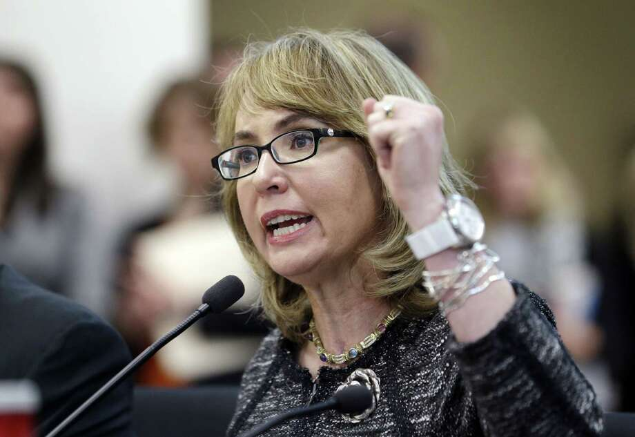 In this Jan. 28, 2014, file photo, former Arizona Congresswoman Gabrielle Giffords pumps her fist as she testifies before a Washington state House panel in Olympia, Wash. Giffords will begin a nine-state tour in Maine on Tuesday, Oct. 14, 2014, where she will advocate for tougher gun laws that she says will help protect women and families. Giffords, who was severely wounded by a gunman in 2011, will seek to elevate the issue of gun violence against women and push for state and federal action to make it more difficult for domestic abusers to get a hold of firearms. Photo: (AP Photo/Elaine Thompson, File) / AP