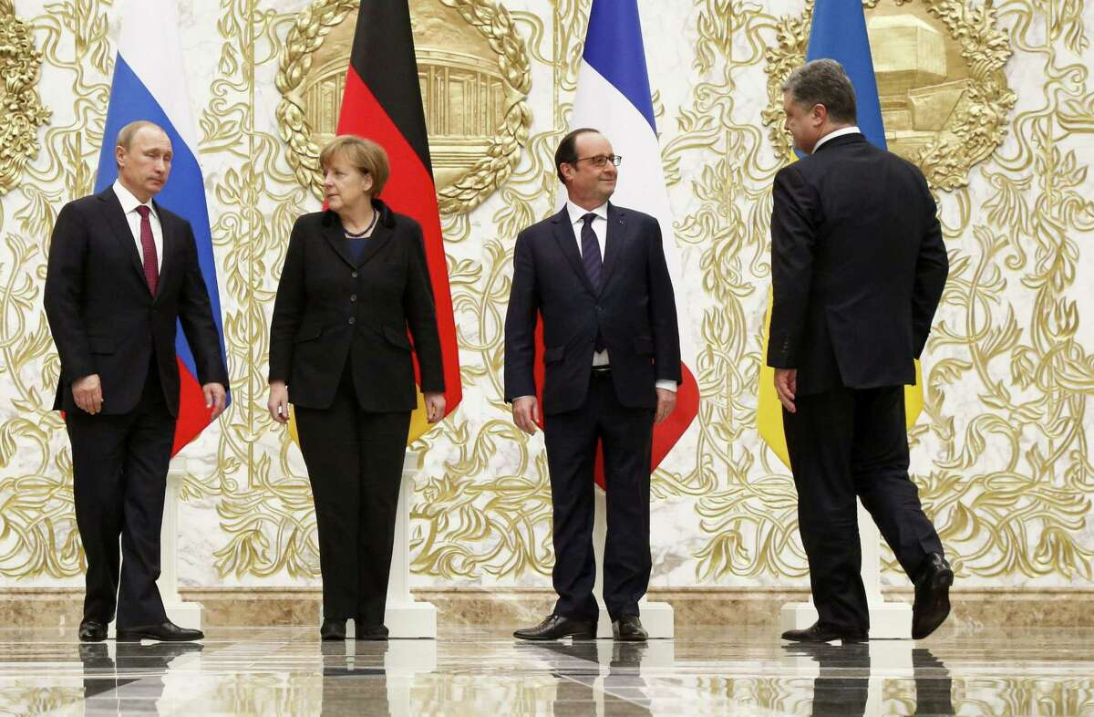 From the left : Russian President Vladimir Putin, German Chancellor Angela Merkel, French President Francois Hollande, and Ukrainian President Petro Poroshenko arrive to pose for a photo during a time-break in their peace talks in Minsk, Belarus, Wednesday, Feb. 11, 2015. Leaders of Russia, Ukraine, France and Germany are gathering for crucial talks in the hope of negotiating an end fighting between Russia-backed separatist and government forces in eastern Ukraine. (AP Photo/Alexander Zemlianichenko)